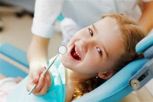 little girl happy sitting in pediatric dentist chair
