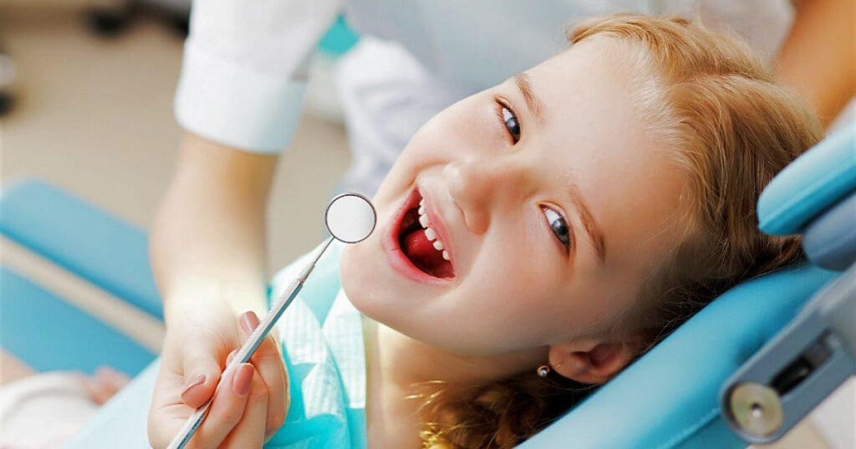 little girl happy sitting in pediatric dentist chair